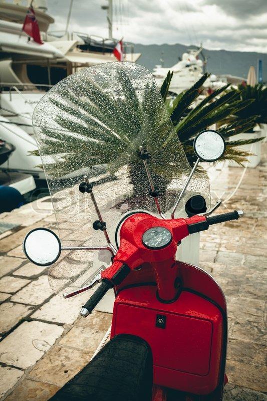 Closeup photo of red scooter bike got wet in rain, stock photo