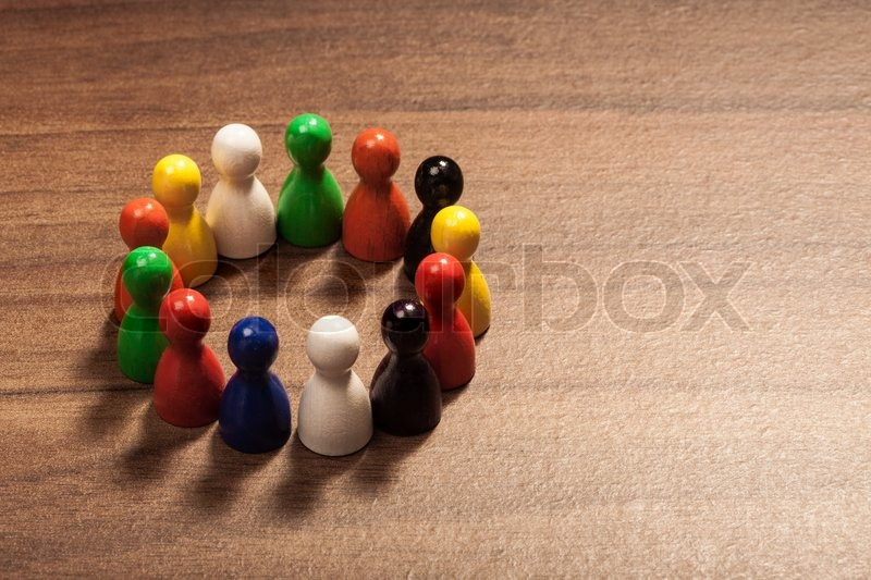 Circle of diversity, friends, colorful toy pawns. Concept on wood table, stock photo