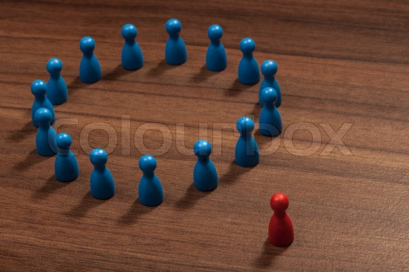 Left outside the circle. Concept with toy pawn figurines on wood table, stock photo