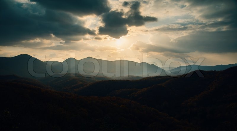 Landscape of mountains in the evening. Cloudy weather, sun sets over the mountains, stock photo
