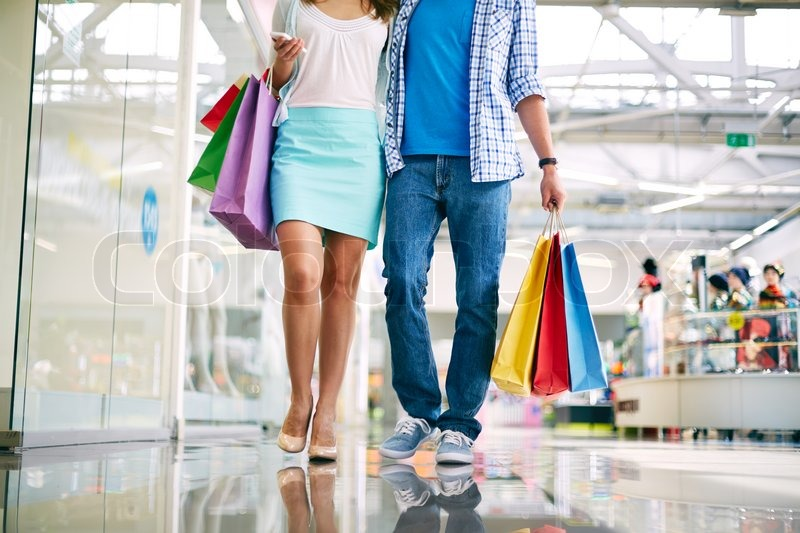 Legs of young couple shopping in trade center, stock photo