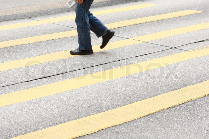 A lone man crossing the pedestrian lane, stock photo