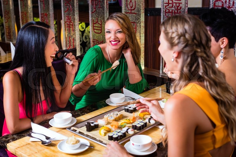Young people eating sushi in Asian restaurant, stock photo