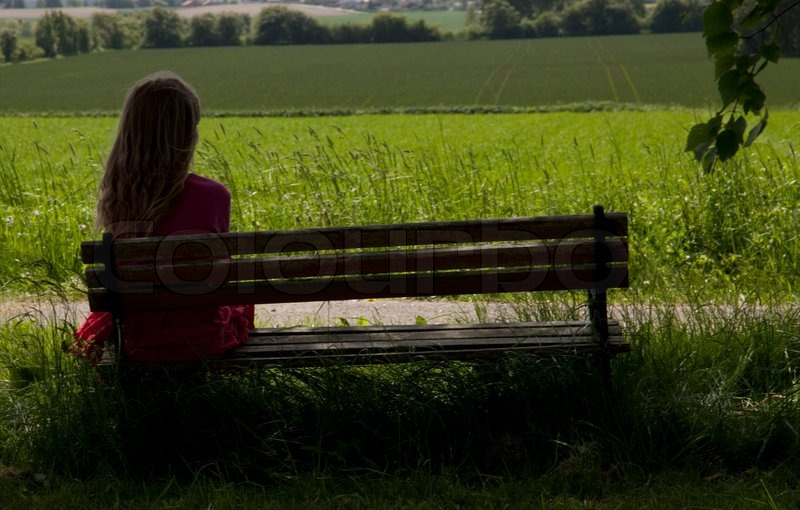 Lonely Girl Sitting On A Bench In A Park Stock Photo