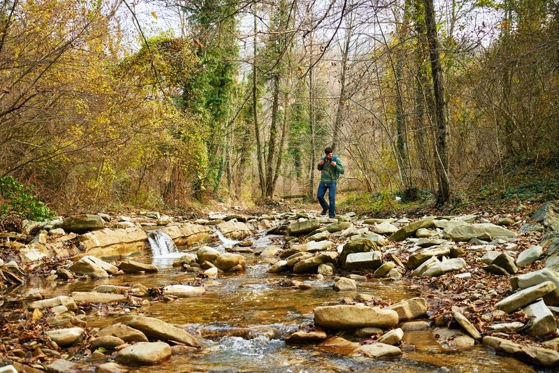 Hiker young man with backpack crossing a river on stones in autumn forest. Hiking and leisure theme, stock photo