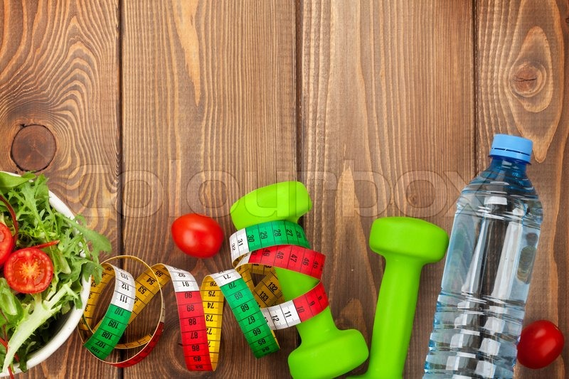 Dumbells, tape measure and healthy food over wooden background. Fitness and health. View from above with copy space, stock photo