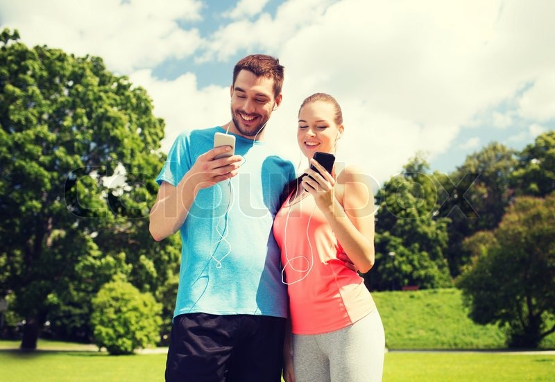 Fitness, sport, training, technology and lifestyle concept - two smiling people with smartphones and earphones outdoors, stock photo