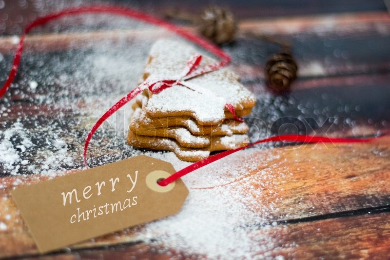 Merry Christmas On A Tag With Homemade Ginger Bread Cookies Sprinkled Powdered Sugar Rustic Background Greeting Card