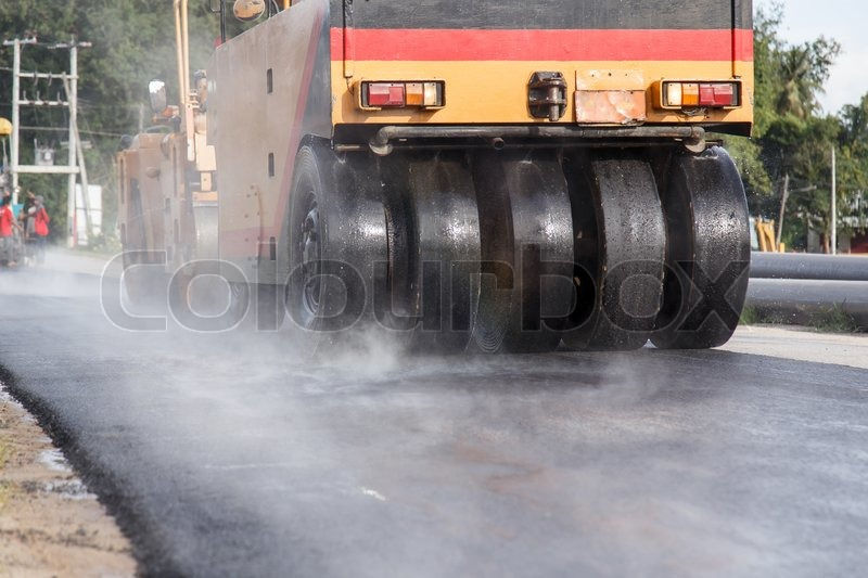 Road roller and asphalt paving machine at construction site, stock photo