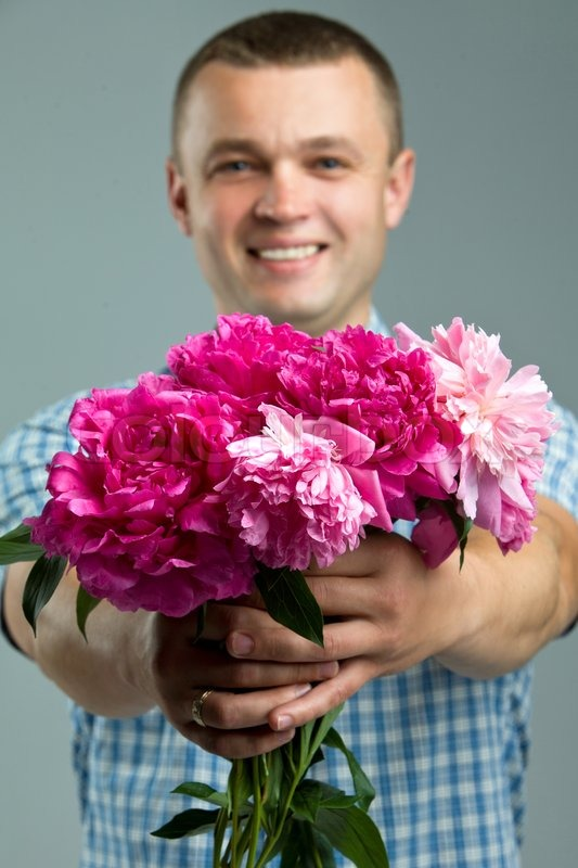 Greetings. Man giving bouquet of flowers. | Stock Photo | Colourbox