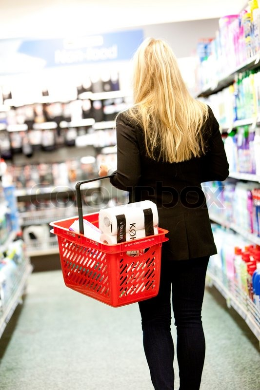 A young blond, caucasian woman in a supermarket carrying a shopping basket, stock photo