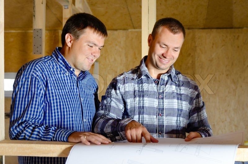 Two builders discussing a building plan as they stand in the interior of a new build timber frame house still under construction, stock photo