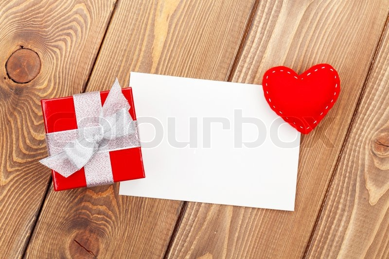 Photo frame or greeting card with gift box and toy heart over wooden table background, stock photo