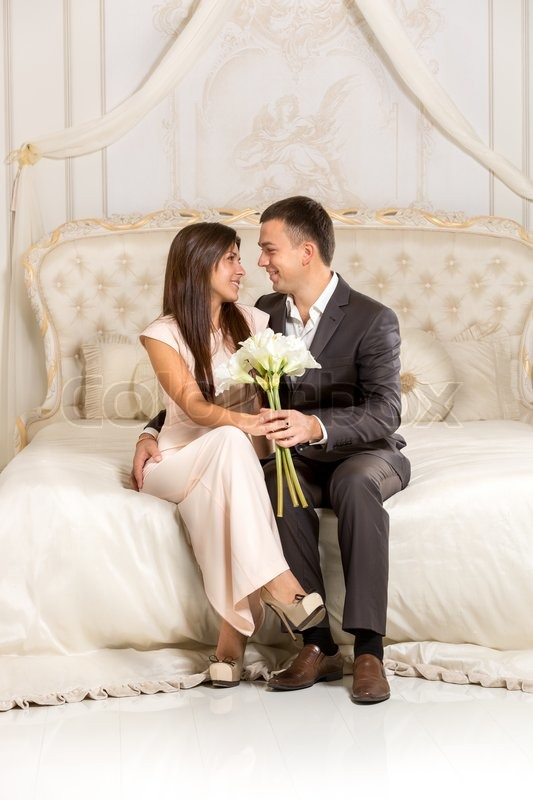 Beautiful romantic couple in love sitting on bed in luxurious room   Stock  Photo   Colourbox. Beautiful romantic couple in love sitting on bed in luxurious room