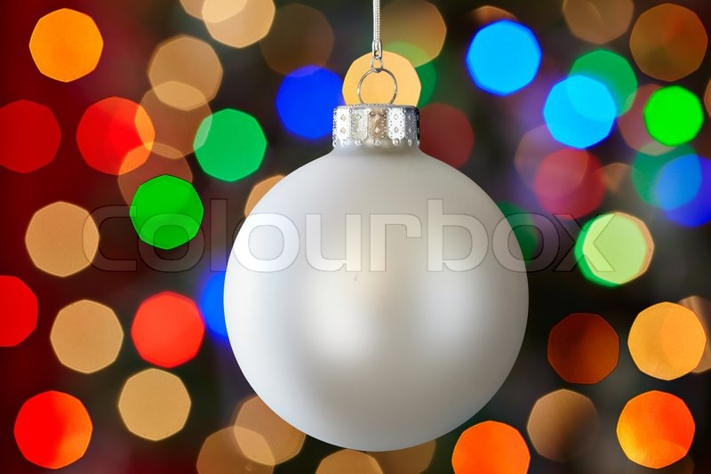 white christmas ornament over colorful multicolored christmas light