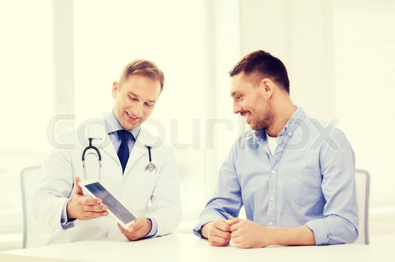 Healthcare, technology and medicine concept - smiling doctor with tablet pc computer and patient in hospital, stock photo