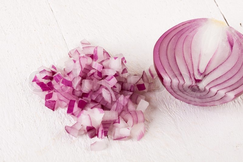 Heap of fresh finely diced red onion with a peeled half ...