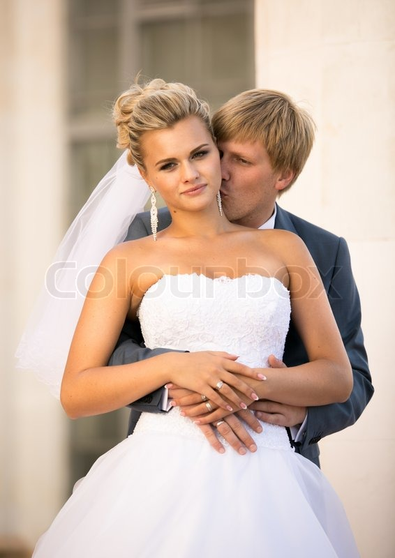 Portrait of young groom hugging blonde bride from back on ...