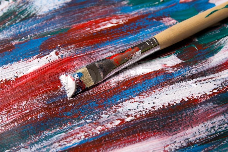 Old brush on acrylic paint background with blue and red strokes, stock photo