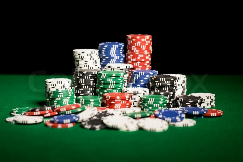 Gambling, fortune, game and entertainment concept - close up of casino chips on green table surface, stock photo