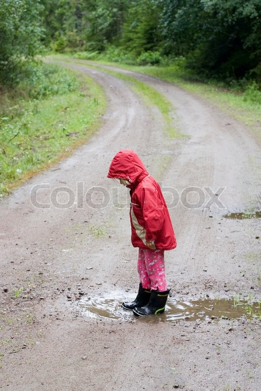 a little 4 year old girl is standing in a rain pu ddle on