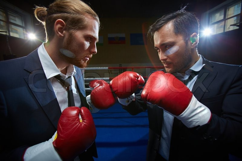 Angry men in suits and boxing gloves attacking one another, stock photo