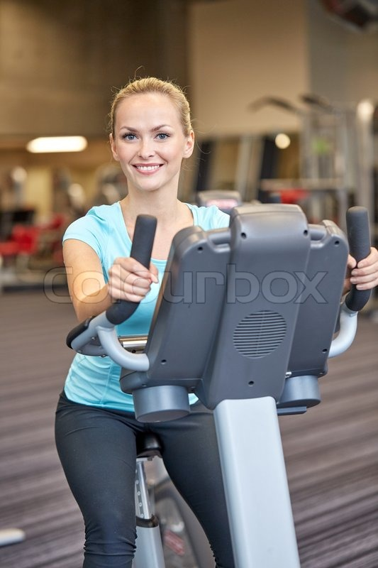 Sport, fitness, lifestyle, technology and people concept - smiling woman exercising on exercise bike in gym, stock photo