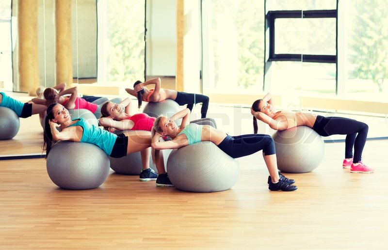 Fitness, sport, training and lifestyle concept - group of smiling women with exercise balls in gym, stock photo