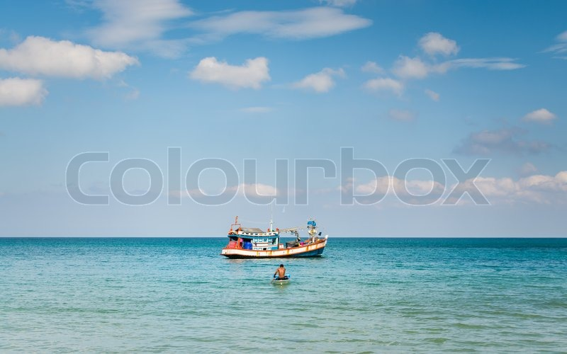 A man paddling a little boat from fishing boat under blue sky, stock photo
