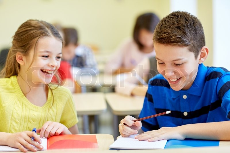 Education, elementary school, learning and people concept - group of school kids with pens and notebooks writing test in classroom, stock photo