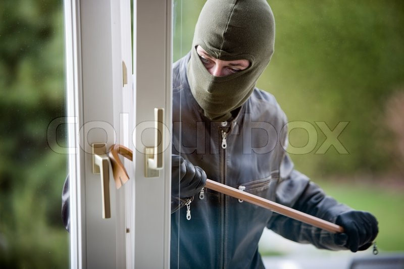 Stock image of 'Burglar breaking into a house through the window'