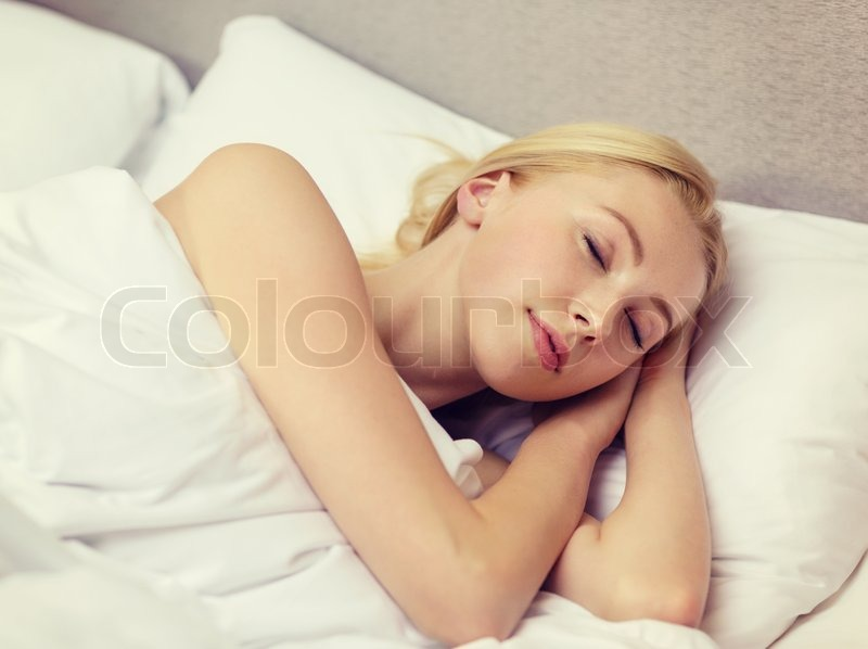 Stock image of 'hotel, travel and happiness concept - beautiful woman sleeping in bed'