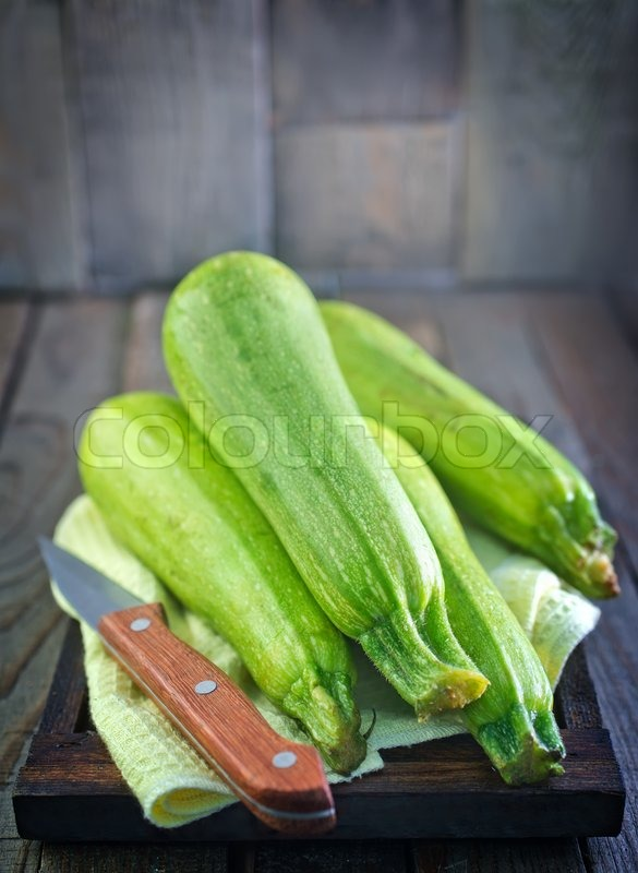 Stock image of 'raw zucchini on wooden tray and on a table'
