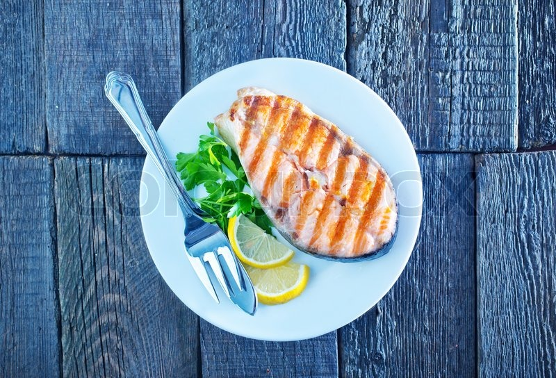 Stock image of 'grilled salmon steak with lemon on white plate'
