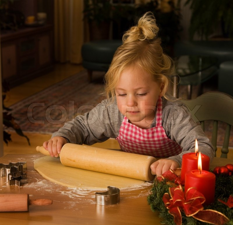 Child baking Christmas cookies during Advent, stock photo