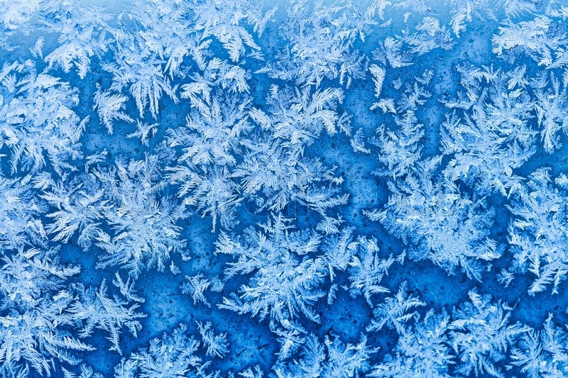 Snowflakes and frost pattern on window in cold winter evening close up, stock photo
