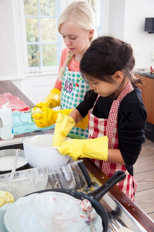 Two Girls Cleaning Dirty Kitchen Wares Stock Photo