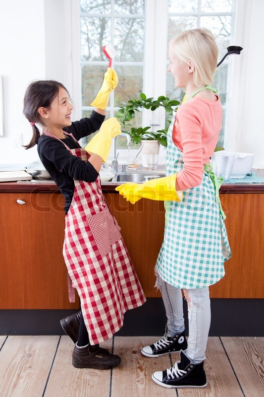 Two Girls Playing Instead Of Cleaning The Kitchen Stock
