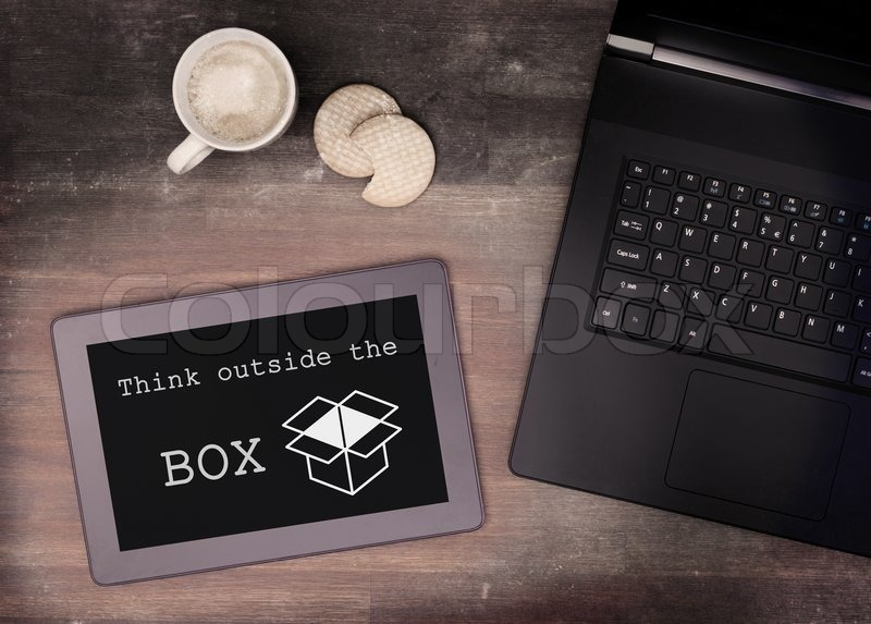 Tablet touch computer gadget on wooden table, think outside the box, vintage look, stock photo