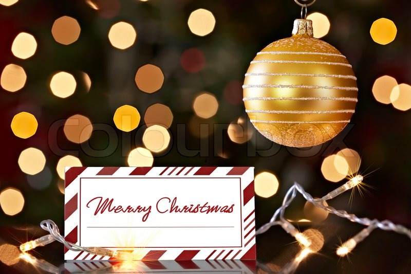 gold christmas ornament and colorful red striped happy holiday card christmas lights bokeh background stock photo colourbox
