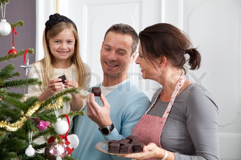 A Happy Family Eating Chocolate On Christmas Day Stock