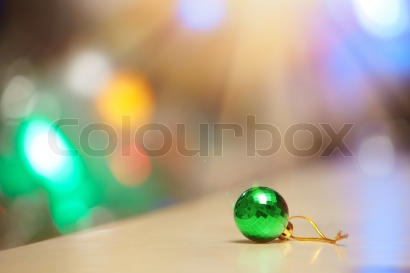 Green Christmas ball and illuminated background, stock photo