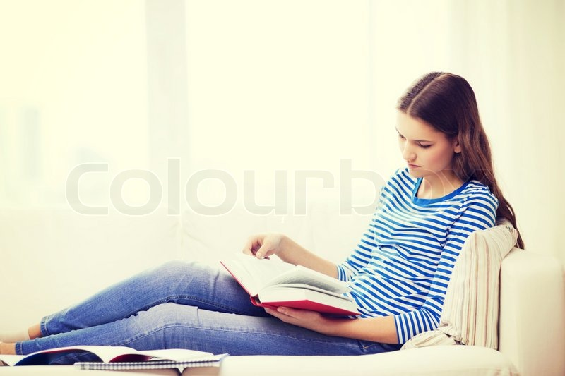 Leasure and home concept - calm teenage girl woman reading book and sitting on couch at home, stock photo