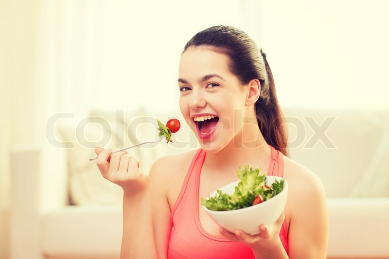 Healt, dieting, home and happiness concept - smiling sporty teenage girl with green salad at home, stock photo