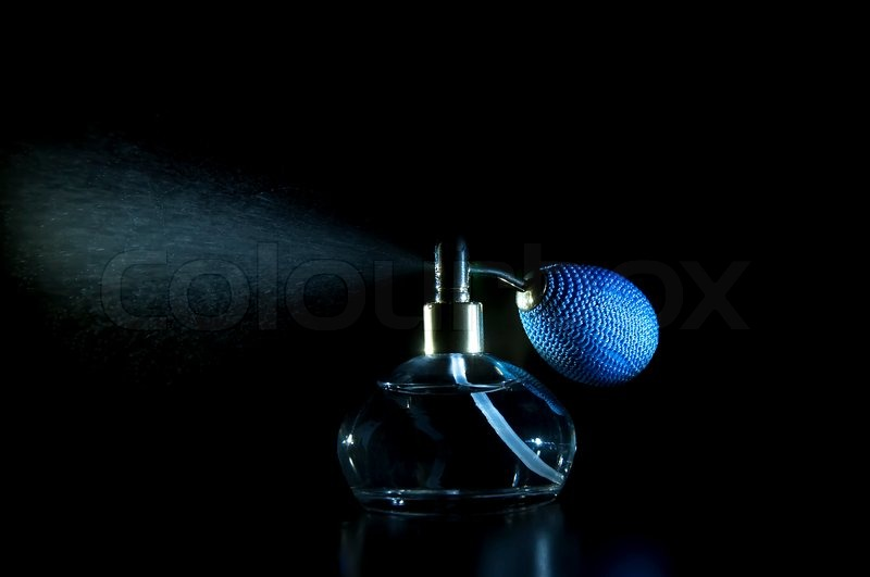 Vintage antique perfume bottle with effect of perfume spray on black background, stock photo