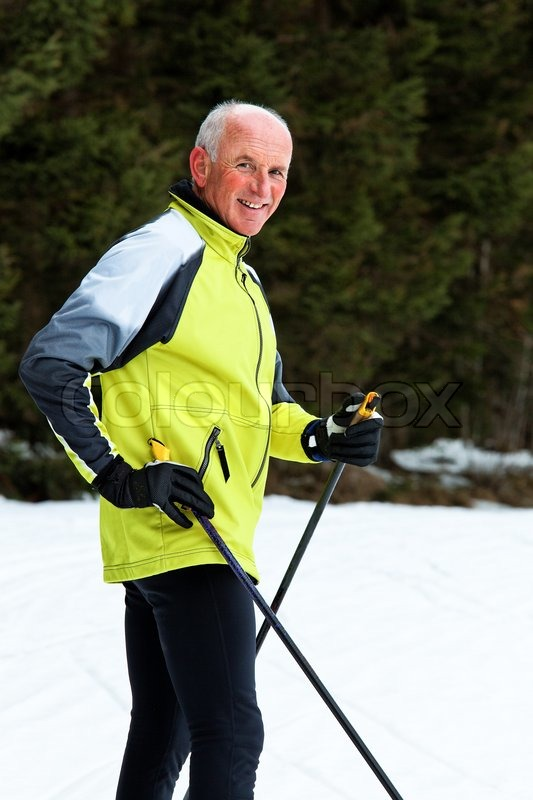 Senior at the snow in winter on cross country skis, stock photo