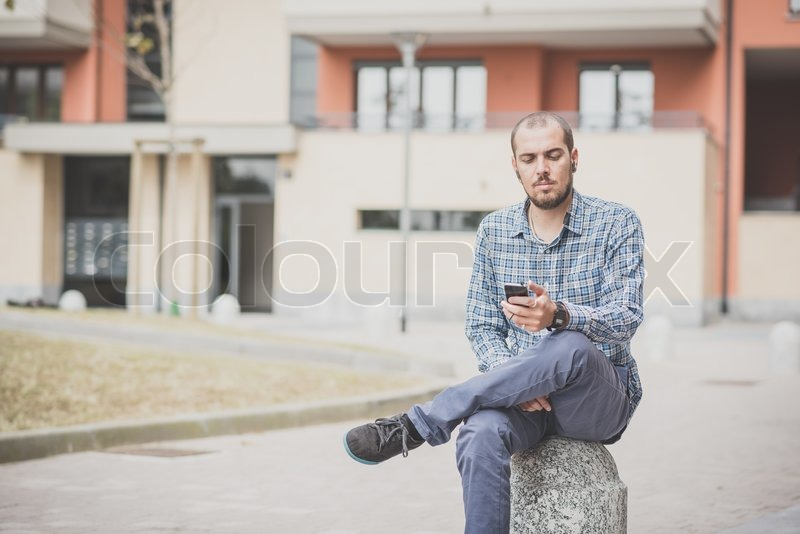 Handsome hipster casual multitasking modern man listening music and using smartphone in the city, stock photo