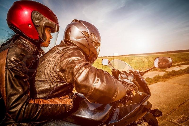 Couple Bikers in a leather jacket riding a motorcycle on the road, stock photo