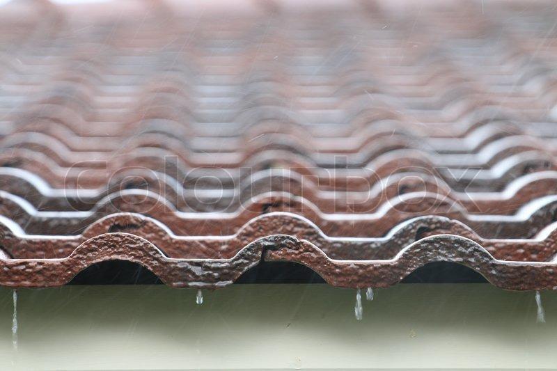 Falling Rain drop on brown brick roof, close up. , stock photo