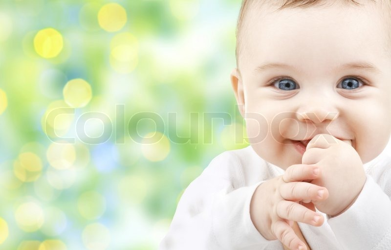 Children, people, infancy and age concept - beautiful happy baby over green lights background, stock photo